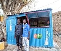 Dankouma Daoude & his friend outside his shop selling herbal tobacco for shisha pipes