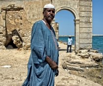 Adil in Suakin, with ruins of the old town built of coral behind him