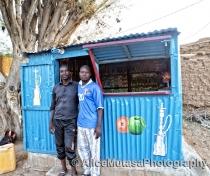 Dankouma Daoude & his friend outside his shop selling herbal tobacco for shisha pipes